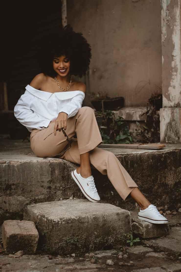 photo of smiling woman sitting on concrete block posing
