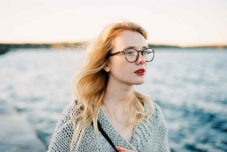 woman in gray knit cardigan and eyeglasses